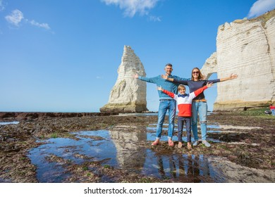 Happy family of three people standing on the beach in Etretat. France