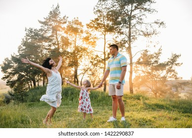 Happy family of three persons walking the grass in the park.