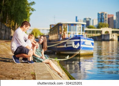 Happy family of three sitting on the bank of the Seine and enjoying their trip to Paris, France