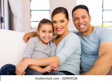 happy family of three sitting on the couch at home