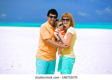 Happy family of three with sun glasses standing on the beach