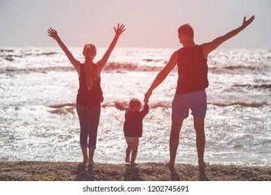 Happy family of three at sunset backlight