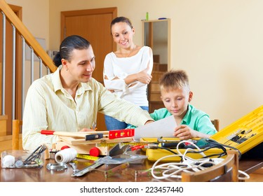 Happy family of three with teenage boy doing something with the working tools