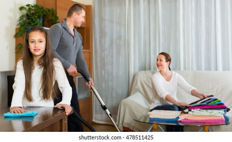 Happy family of three tidying up a room all together. Focus on girl