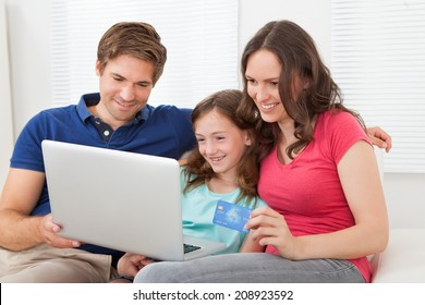 Happy family of three using laptop and credit card to shop online on sofa at home
