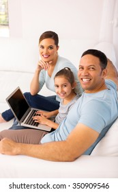 happy family of three using laptop computer while relaxing on sofa at home