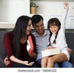 Happy Family time at home. Mother, father and daughter having fun in the living room. Feeling happy and complete. Cheerful family at home sitting in sofa. Smiling young parents and their child