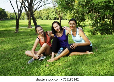 The happy family time. The mother and two Daughter relax on the weaken in the green park with sport wear. The happy face of women in green park