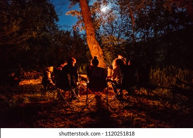 Happy family time outdoors in forest near bonfire and tourist tents at campsite. Group of people silhouettes under night sky with stars. Friends travel, enjoy nature holidays at camping place.