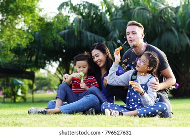 Happy Family time : The parents son and Daughter have a free time in the park on holiday. Children in green nature make soap bubble on summer. Happy family having weekend in summer park