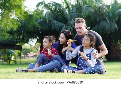 Happy Family time : The parents son and Daughter have a free time in the park on holiday. Children in green nature make soap bubble on summer. Young family with children having fun in nature