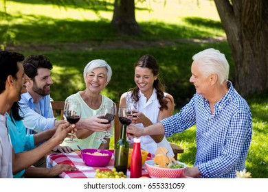 Happy family toasting a glasses of wine in park