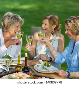 Happy family toasting white wine at dining table in lawn