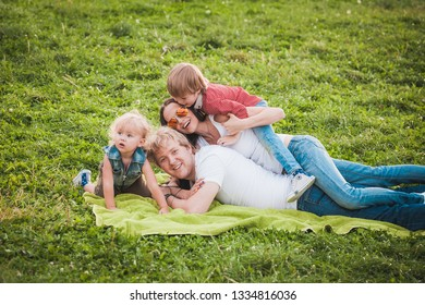 Happy family together in green park in summer. Father hugging wife and sons sitting on green grass