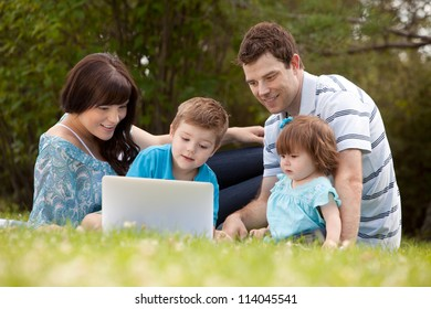 Happy family together outdoors with computer