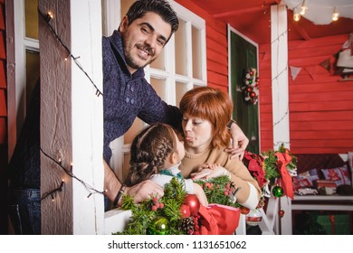 Happy family together. The parents father and mother near red wall and decoration for Christmas arround