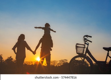 Happy family together, parents with their little child at sunset. Father raising baby up in the airing the sky on a holiday on Chatuchak Park at Bangkok City, Thailand. Concept of friendly family.