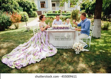 happy family together in picnic, colorful outdoors. Father, mother and two sons. Woman in elegant long dress. Family celebrating wedding anniversary