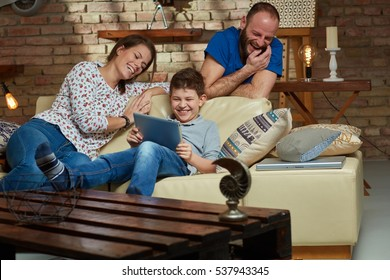 Happy family together, son playing on tablet, parents watching, laughing.