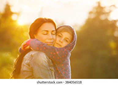 Happy family together, young beautiful mother closing eyes in pleasure hugging her cute little daughter, bright sunny day, happy motherhood