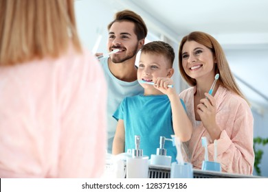 Happy family with toothbrushes near mirror in bathroom. Personal hygiene
