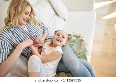 Happy family. Top view of adorable little girl lying on mother laps while she holding her hands and smiling