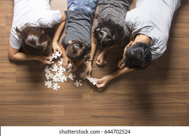 Happy family top view lying on floor with solving a jigsaw puzzle problem and enjoying their leisure time activities.  in her room at home