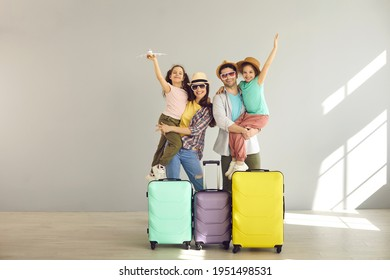 Happy family tourist portrait. Father, mother and two daughters ready for travel flight posing to camera with suitcase waiting for aircraft arrival. Airport departure studio background with copy space