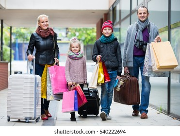 Happy family of tourists with kids carrying the shopping bags outdoors