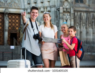 Happy family of tourists with two kids looking for destination with city map