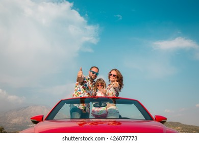 Happy family travel by car in the mountains. People having fun in red cabriolet. Summer vacation concept
