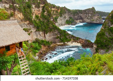 Happy family travel lifestyle. Mother with child sit on steps of traditional house on tree, look at Atun beach, Nusa Penida island. Popular travel destination on Bali holidays. Indonesian background.