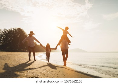 Happy family travel on beach in holiday,Summer vacations. Happy family are having fun on a tropical beach in sunset. Father and mother and children playing together outdoor on beach.