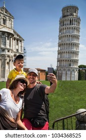 Happy family traveler taking selfie and having fun in front of the famous leaning tower in Pisa (Unesco). Feather, mother and little boy making self portrait by smartphone. Vacations in Italy, Tuscany