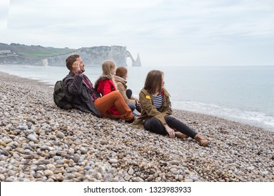happy family trip -  smiling dad with mom and two daughters sitting on the beach of  Etretat. France