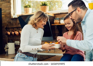 Happy family trying food that mother has prepared in the kitchen.