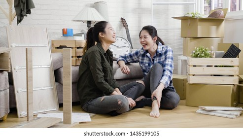 Happy family two asian sisters having fun at new home cardboard boxes in house. Young women friends roommates purchase real estate move in. ladies relax chatting while assembling furniture together.