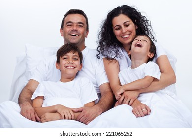 Happy family with two boys cuddling in bed on a lazy morning - laughing with joy