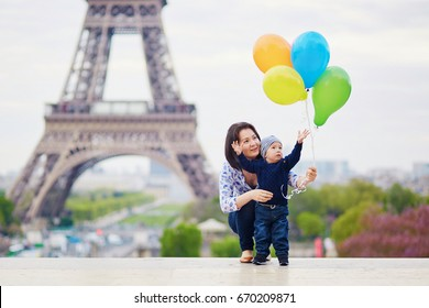 Happy family of two with bunch of colorful balloons in Paris near the Eiffel tower. Mother and little son enjoying their vacation in France