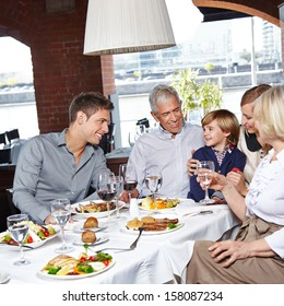 Happy family with two children and grandparents eating in a restaurant