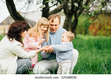 Happy family with two children having fun in the apple-garden and playing with flowers of apple blossom in their hands on a spring day.