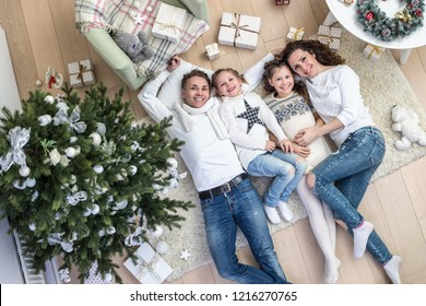 Happy family with two children lies under the Christmas tree with gifts on the carpet. View from above