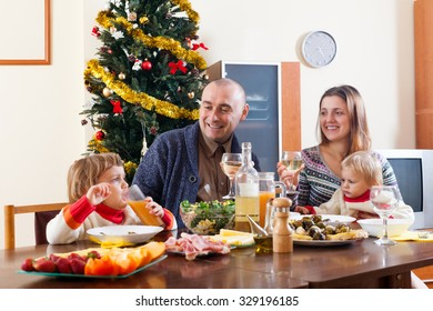 Happy family with two children near Christmas tree  over celebratory table at home
