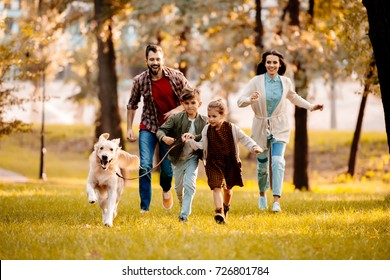 Happy family with two children running after a dog together in autumn park