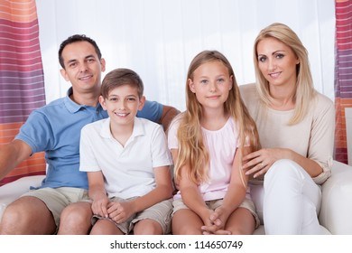 A Happy Family With Two Children Sitting On Sofa At Home