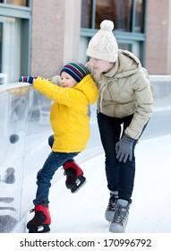 happy family of two enjoying ice skating at winter