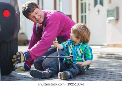 Happy family of two: father and adorable little boy repairing car and changing wheel together on warm day, outdoors.
