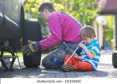 Happy family of two: father and adorable little preschool boy repairing car and changing wheel together on warm day, outdoors.