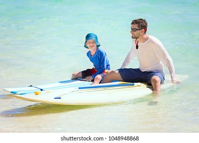 happy family of two, father and his son, enjoying active vacation at fiji island resting after stand up paddleboarding