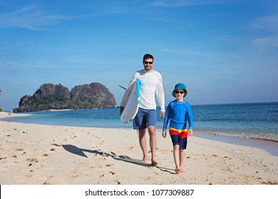 happy family of two, father and son, walking at the beach holding surf board, adventure vacation concept